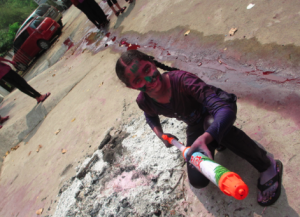 Anushree on the Attack On the left are the ashes from the previous night's Holi bonfire, on her right is a stream of colored water.